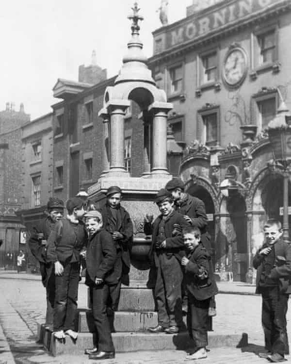 A group of boys gathered for a photograph round a small but ornate drinking fountain, some of them holding up cups of water