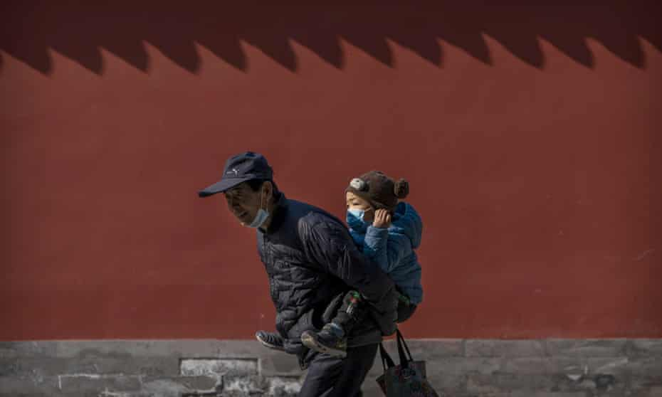 An elderly man carries a young boy on his back as he walks in a public park in Beijing