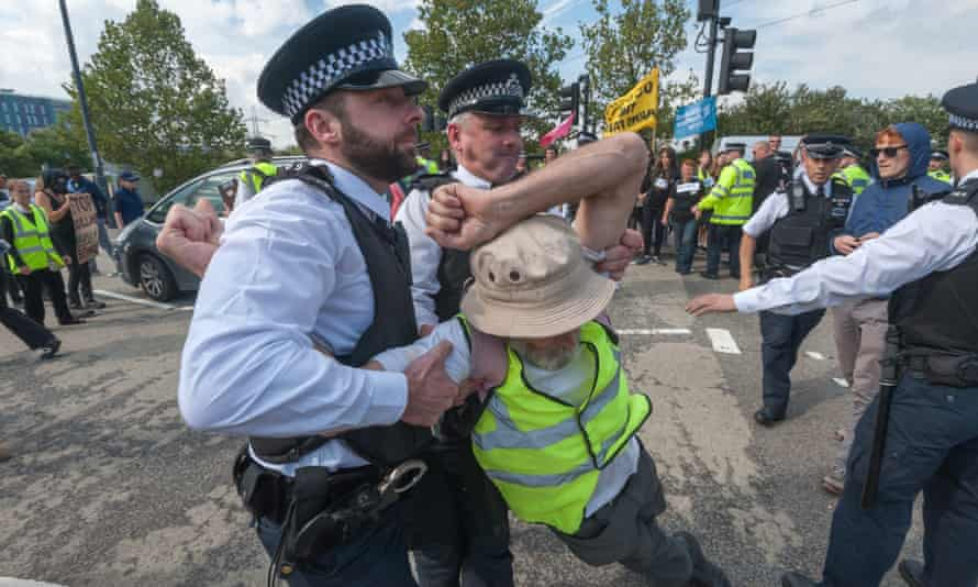 Police pull a protester off the road outside the DSEI exhibition
