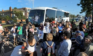 Protesters block a bus carrying Q society supporters from leaving a pick up stop in Melbourne on Friday.
