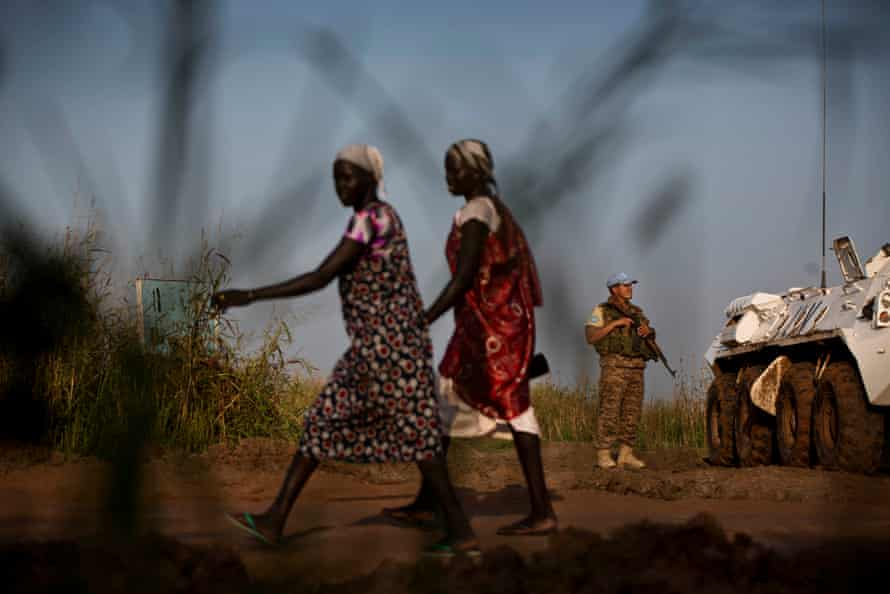 Two women walk past a UN peacekeeper outside the protection of civilian camp in Bentiu, South Sudan