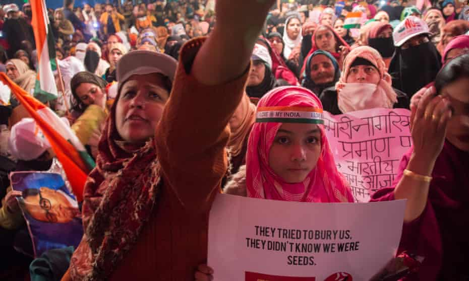 Women protesting in Shaheen Bagh, one holding sign reading: 'They tried to bury us. They didn't know we were seeds.'