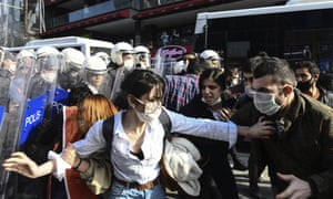 Turkish police officers, in riot gear, and wearing face masks for protections against the spread of the coronavirus, scuffle with protesters during a demonstration in Istanbul, Tuesday
