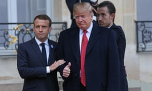 Emmanuel Macron holds Donald Trump's arm as he gives a thumbs up.