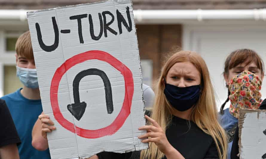 A student holds a placard reading 'U-turn' as she takes part in a protest march in Codsall near Wolverhampton.