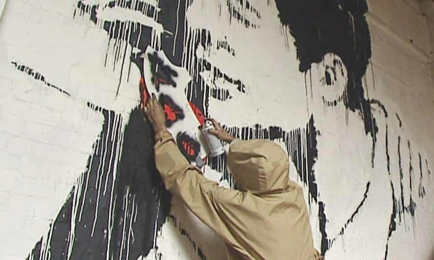 Artist purporting to be Banksy stencils a black insect on to a wall