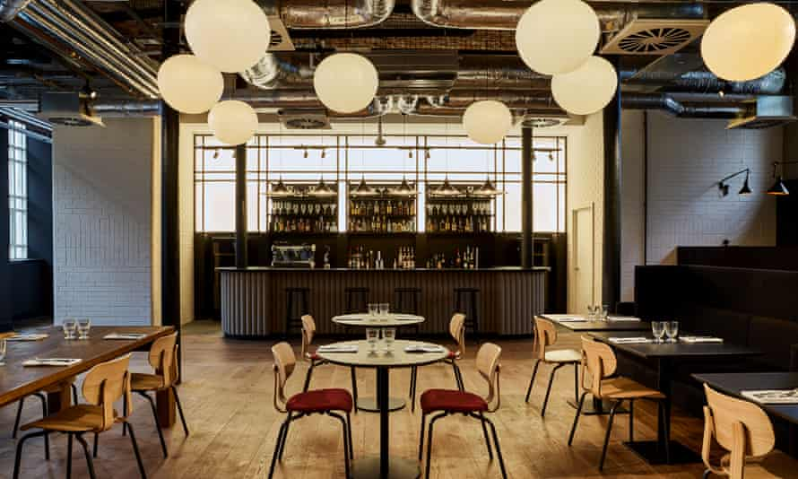 The dining room with exposed pipework on the ceiling and large round lights at wooden floors at Hotel Indigo, Dundee