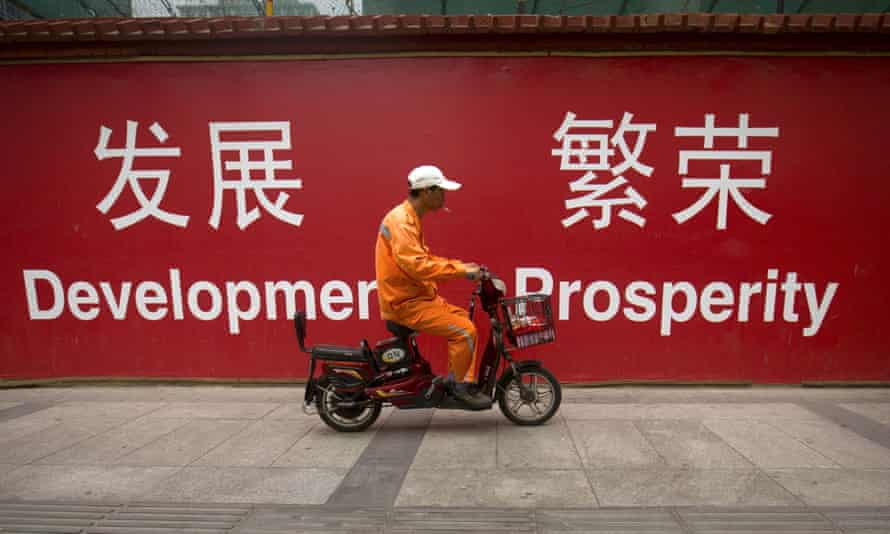 A maintenance worker in China in front of a sign saying Development and Prosperity.