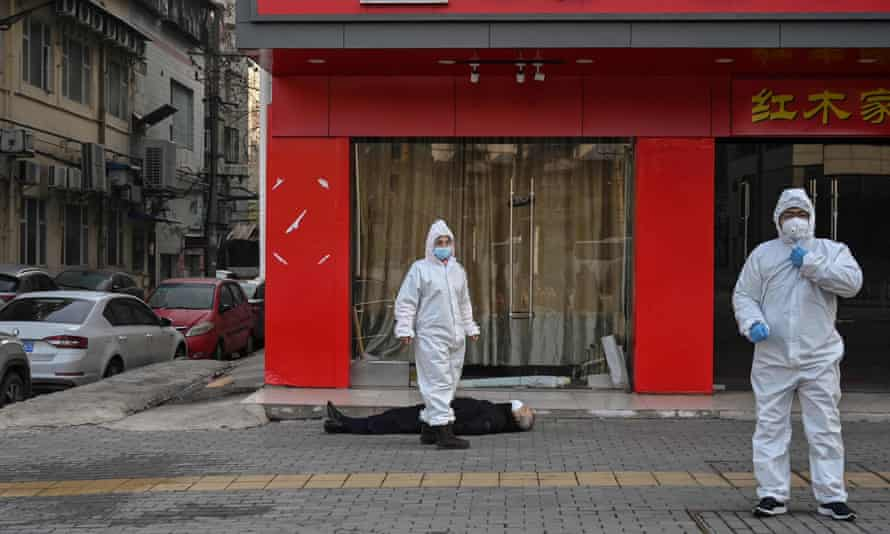 Emergency staff in protective suits check the body of a man who collapsed and died in the street in Wuhan on Thursday.