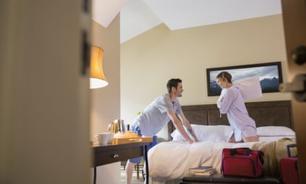 Couple playing on bed in hotel room