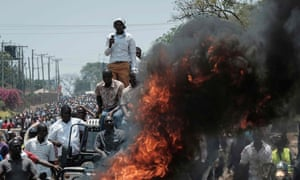 Protesters stand on a car by a fire as they take part in a demonstration in Kisumu