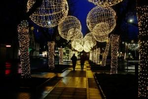 People walk under the Christmas street illuminations in Ogre, Latvia, on 22 December