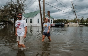A couple walk through a flooded neighbourhood in Narco, Louisiana.