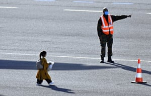 A tiny girl makes her way across the tarmac with a man in a high visibility vest pointing the way.