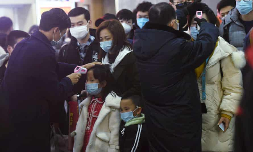 Staff check temperatures of the passengers arriving from Wuhan at Hangzhou railway station.