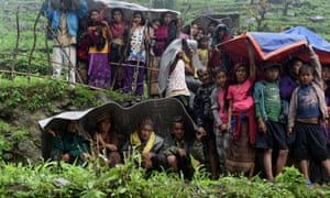 Nepalese villagers shelter from rain as an Indian army helicopter delivers aid