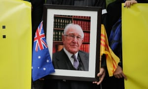Members of the Vietnamese community holds signs and a photograph aloft outside of Scots Church during the State Funeral for the Right Honourable Malcolm Fraser on March 27, 2015 in Melbourne.