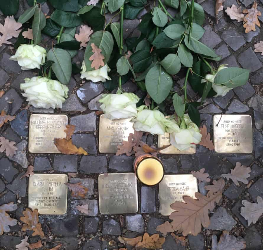 A candle and roses laid on a set of Stolpersteine in Berlin at a commemorative ceremony marking the 80th anniversary of Kristallnacht.