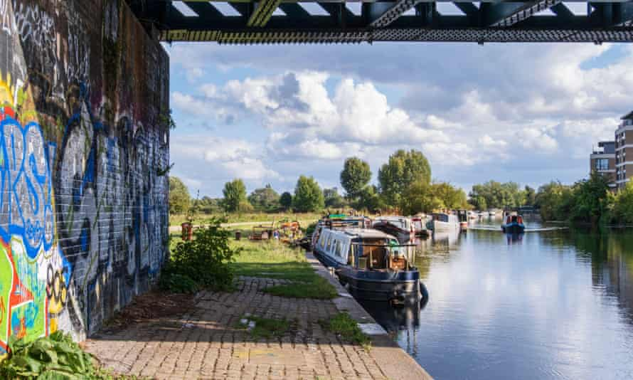 UK, London. Urban landscape - houseboats on the River Lea navigable canal section with graffiti under a railway bridge and a clear summer sky2D35G0T UK, London. Urban landscape - houseboats on the River Lea navigable canal section with graffiti under a railway bridge and a clear summer sky