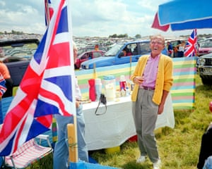 A man in a mustard cardigan and pink shirt laughs during a picnic at the Epsom Derby, from the exhibition The British Abroad by Peter Dench at the POP Galleries