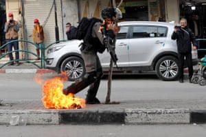 An Israeli border policeman is struck with a molotov cocktail thrown by Palestinian demonstrators during a protest against Donald Trump's Middle East peace plan.