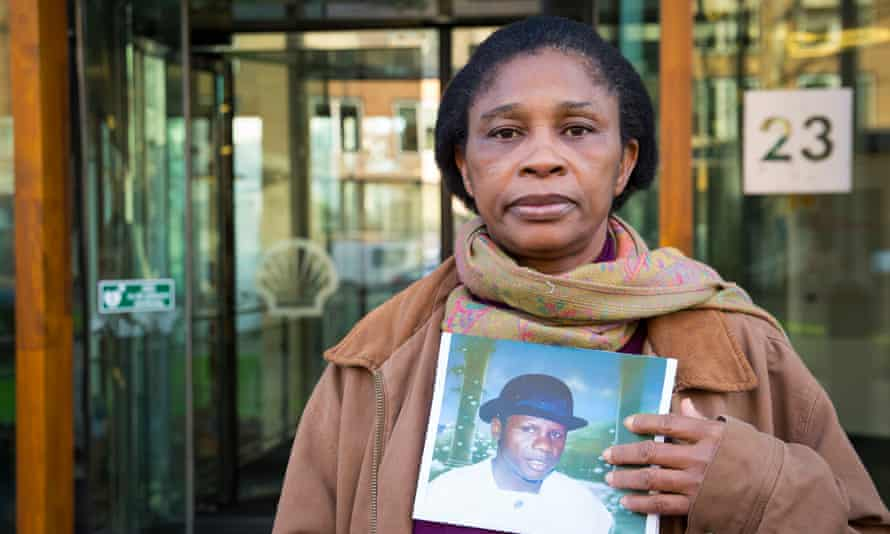 Esther Kiobel poses with a picture of her late husband, one of nine men executed by Nigeria's military government after a peaceful uprising in 1995 against Shell's widespread pollution in Ogoniland