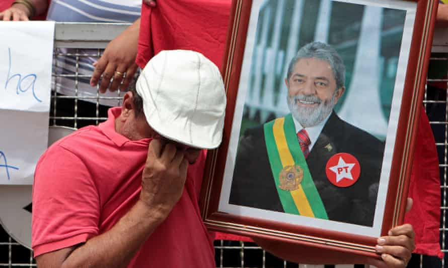 A Lula supporter weeps as he holds a photo of the former president during a rally in São Paulo.