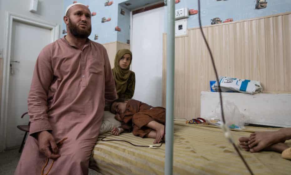 Fareed Ullah sits next to his son Taha, a thalassaemia patient, at Hamza Foundation in Peshawar, Pakistan.