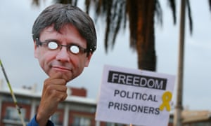 A man raises a mask depicting Carles Puigdemont during a protest in front of Germany's consulate in Barcelona