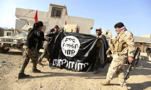 Iraqi soldiers hold up a captured Isis flag at a village near Mosul in 2016