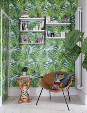 Book nook: the hallway's leafy wallpaper extends into the living room, defining a reading corner in previously unused space.