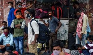 Os trabalhadores migrantes esperam na beira da estrada em 11 de junho para serem transferidos para uma estação ferroviária antes de embarcarem em trens especiais para os estados de Bihar e Jharkhand, na Índia, depois que o governo facilitou um bloqueio nacional.