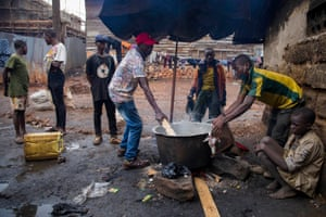 Musa Ssebagala and some helpers prepare lunch for street children in Kisenyi.
