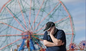 Evan Demaree, an emergency medical services attendant and firefighter holds his phone to his ear while talking to a friend on a windy day at the Coney Island boardwalk in April.