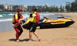 Volunteer surf lifesavers perform a rescue drill at Manly Beach. Australia's hotter, drier weather is leading to more people in the water and more drownings, lifesavers warn.