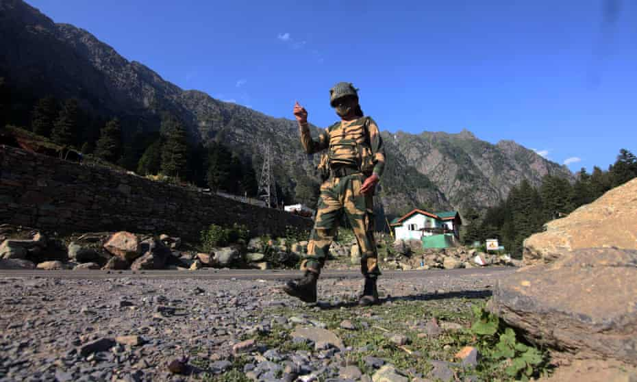 An Indian border security force soldier walks near a check post along the Srinagar-Leh National highway on Tuesday, following deadly clashes along the disputed border with China.