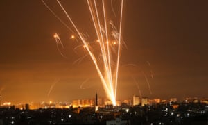 Rockets fired towards Israel from Beit Lahia in the northern Gaza strip light up the night sky on 14 May.
