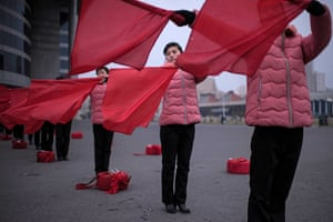 Members of a propaganda troupe wave flags as they perform as part of a 200-day campaign aimed at sustaining a new economic plan