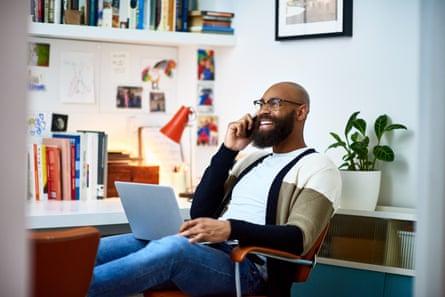 Pria dengan laptop berbicara di ponsel