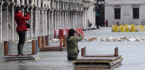 Visitors take pictures in St Mark's square in December 2008, after it had been hit by one of the highest tides in the city's history.