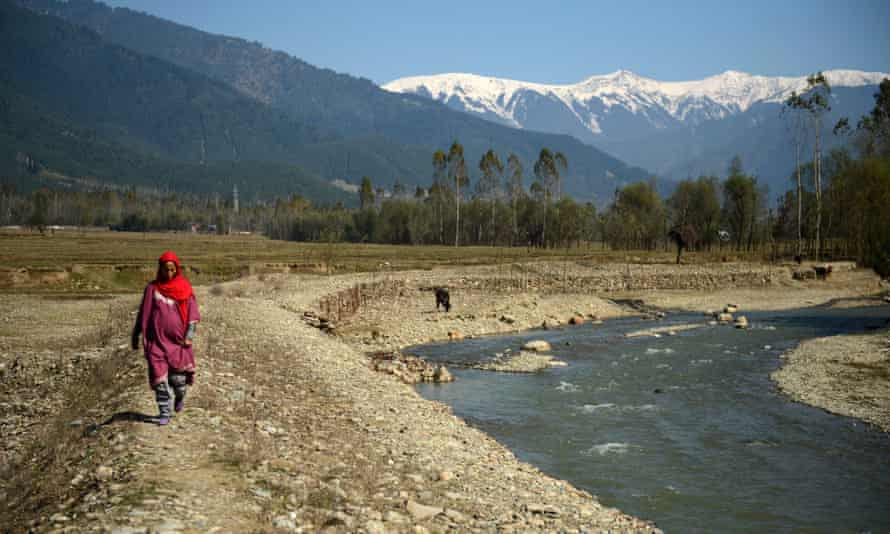 A Kashmiri villager walks past what used to be a pond holding drinking water in the village of Chandigam in the Lolab valley in the foothills of the northern Kashmir Himalayas, where glaciers are melting fast.
