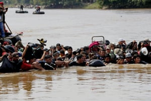 Members of the second migrant caravan, mostly Hondurans, cross the Suchiate river, which separates Guatemala and Mexico, in Tecun Uman, Guatemala