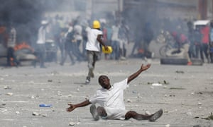 A protester drops to the ground after police fire teargas to prevent demonstrators from marching in Port-au-Prince, Haiti, on 4 October.