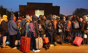 Migrants line-up to register at a processing centre in the Calais camp as the mass exodus from the migrant camp begins