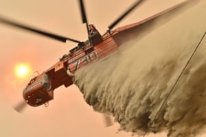 A helicopter drops fire retardant to protect a property in Balmoral, 150 kilometres south-west of Sydney