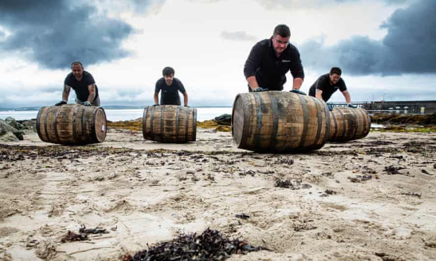 Men rolling barrels up a beach