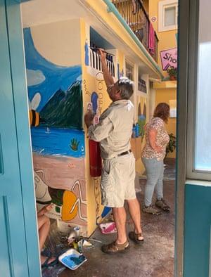 Guest painting murals in the Secret Garden hostel