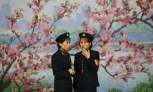 Two railway workers chat in front of a flower mural inside a subway station visited by foreign reporters during a government organised tour in Pyongyang, North Korea October 9, 2015.