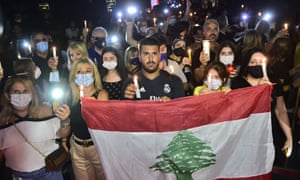 Lebanese people light candles as they gather around the site of explosion to commemorate those who lost their lives