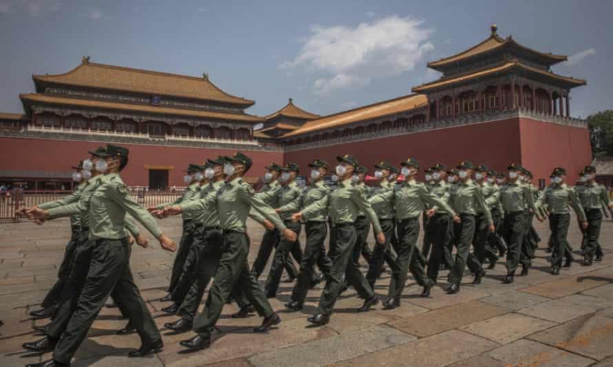 Tentara Tentara Pembebasan Rakyat Tiongkok PLA yang mengenakan masker pelindung berbaris melewati pintu masuk Kota Terlarang